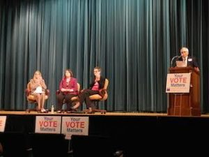 Photo of three women during panel discussion next to speaker at podium